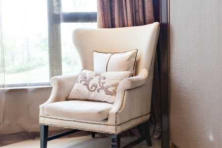 Armchair close to  the window at  a new interiors photo