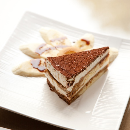A slice of the Italian delicacy tiramisu and several piece of banana on dish photo