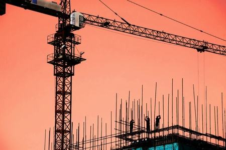Silhouette of construction workers working under Cranes on construction site at dusk photo
