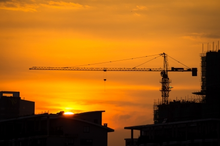 Industrial construction cranes and building silhouettes with sunset photo
