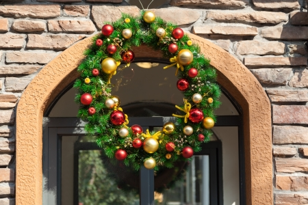 Christmas decorative Wreath with colorful balls Hanging in Front of door photo