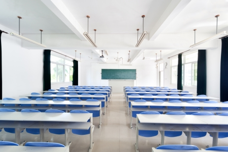 class room: Bright empty classroom with desks and chairs Stock Photo