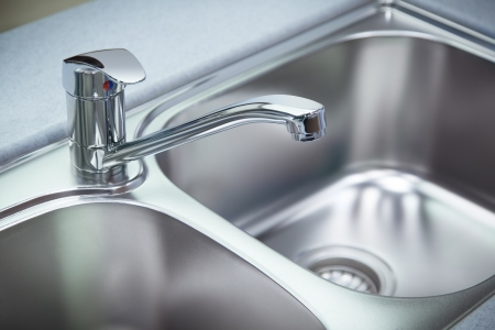 Close up shot for the clean chrome tap and  washbasin in a kitchen photo