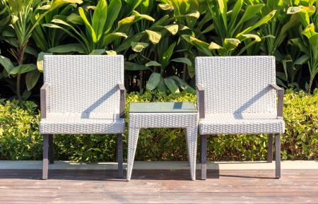 Outdoor furniture rattan armchairs and table on terrace  in a beautiful garden