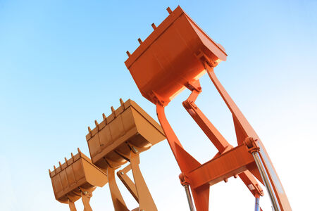 mining equipment: Part of modern yellow excavator machines, the buckets  shovels raised against blue sky in a construction site. Stock Photo