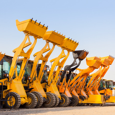 dredging tools: Row of heavy construction excavator machine against blue sky in a construction site. Stock Photo