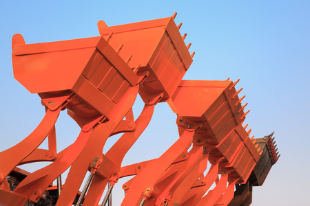 Part of modern yellow excavator machines,the bucketsshovels raised against blue sky in a construction site.