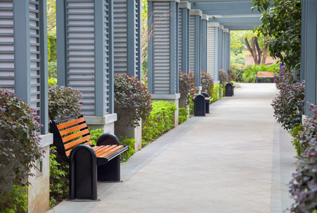 Empty outdoors promenade with resting chairs and bush in a new park,China