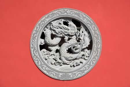 Stone dragon relief - window made of decorated stone relief, ornaments and relief on the red wall from Chinese buddhism temple, Fujian,China.