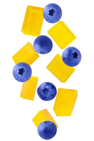 Isolated falling fruits. Falling mango and blueberries isolated on white background with clipping path as package design element.