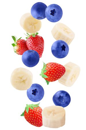 Isolated falling fruits. Falling sliced banana, strawberry and blueberry isolated on white background with clipping path as package design element.