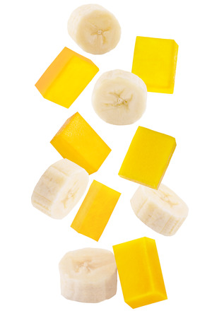 Isolated falling fruits. Falling sliced banana and mango isolated on white background with clipping path as package design element.