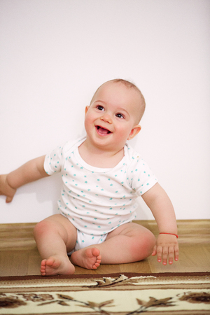 Happy baby boy (1 year old) sitting on floor at childrens room. Archivio Fotografico