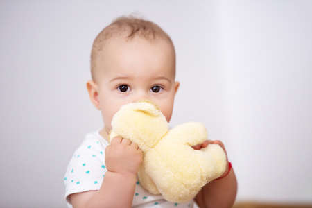 Adorable baby boy lying with plush toy indoor.