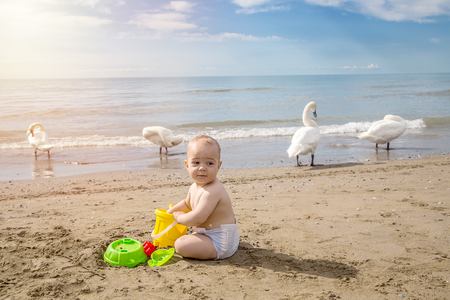 Beautiful child plays in the sand with the games from the beach at sunrise. Travel and adventure concept. Archivio Fotografico - 96361788