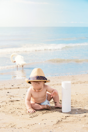 happy kid with dad hat playing with sand on beach on summer vacation. Travel and adventure concept. Archivio Fotografico - 96374903