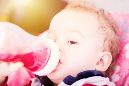 Cute baby drinking water from bottle sitting on chair. Close up portrait.
