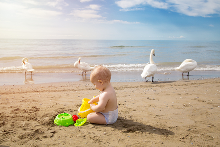 Cute baby plays in the sand with the games from the beach at sunrise. Travel and adventure concept. Archivio Fotografico