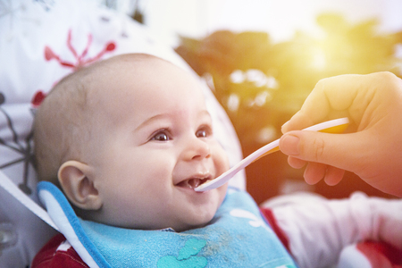 Adorable baby have lunch with spoon at the table. Archivio Fotografico - 96654499