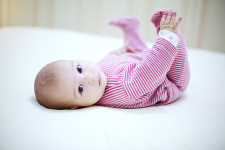 Beautiful baby playing with his legs on the bed in bedroom. Archivio Fotografico