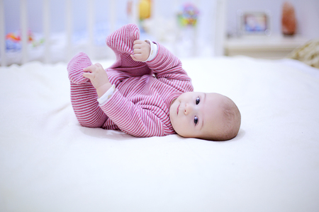 Cute little baby plays with his legs on the bed in bedroom.