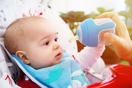 Adorable Curious baby drinks water from the bottle. Happy and emotional. Archivio Fotografico - 96654502