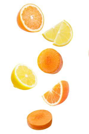 Isolated falling fruits. Falling orange, limon and carrot isolated on white background