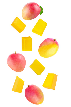 Isolated flying fruits. Whole and cubes falling mango fruit isolated on white background with clipping path as package design element and advertising. Archivio Fotografico - 99206962