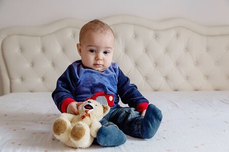 Baby boy in a blue sweater and orange hair sitting on a white bed with a soft toy bear.