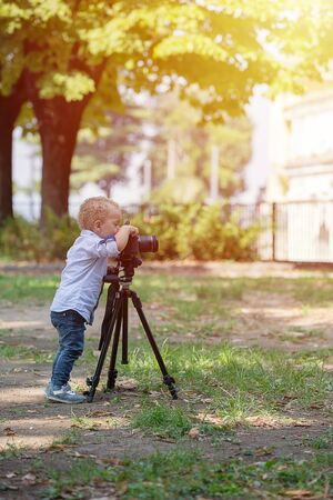 Two years old boy is photographer. Little boy photographing on the camera on tripod in the park.