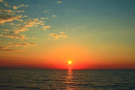 Heldere zonsondergang met gele zon onder het zeeoppervlak