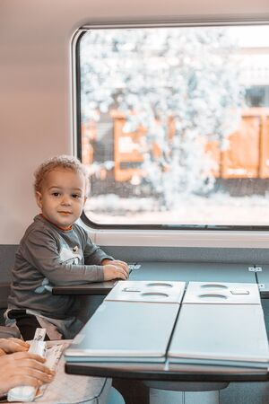 Two years old child sitting at the table and playing while traveling in the trainrailroad. Vacation concept. Zdjęcie Seryjne