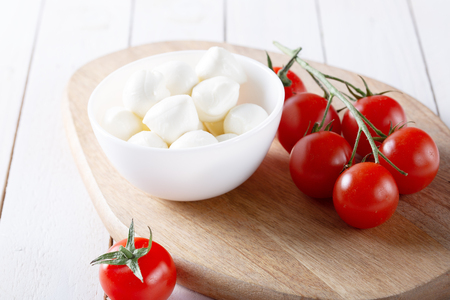 Organic cherry tomatoes and mozzarella in ceramic plate on white background. Top view. Lay Flat. soft focus. Stock Photo