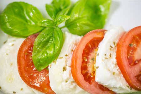 Caprese salad ingredientsfresh with vegetables, herbs and spices on white background, Italian cuisine concept. Soft focus. Imagens