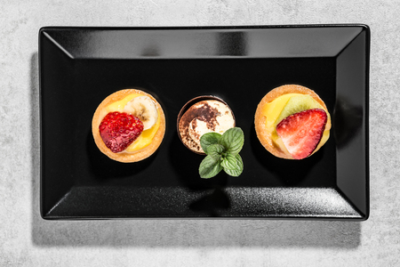 Typical italian pastries stuffed with custard and fresh fruit on white background. Italian cuisine concept.