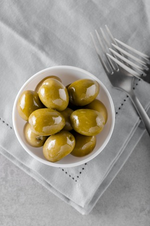 Typical italian green olives in a bowl on concrete table. Concept of appetizer from Italian cuisine. Top view with copy space.