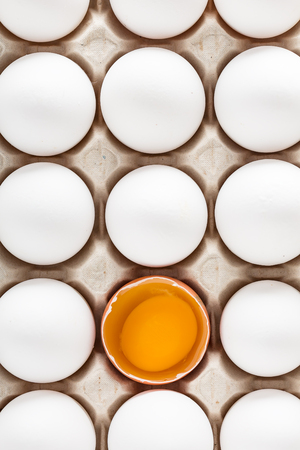 White fresh chicken eggs and one brown egg in a carton box isolated on yellow background. Top view with copy space. Healthy food concept. Selective soft focus.