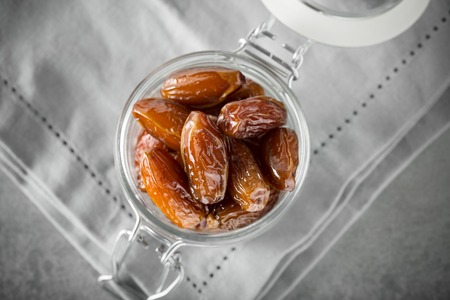 Blessed or kameen ramadan with dates fruit in a glass jar. Typical traditional Iftar food concept in islamic world. Top view with copy space. Selective focus. 写真素材