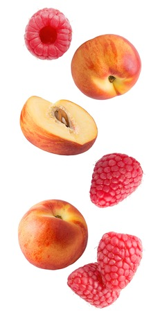 Flying peach and raspberry fruits isolated on white background