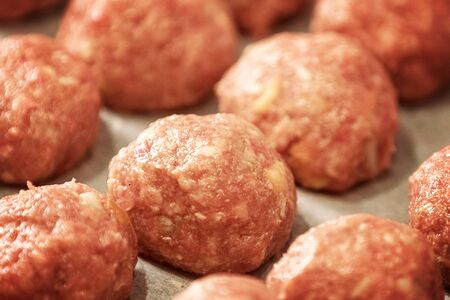 Uncooked dumplings on tray. Fresh minced meat in the form of balls with pepper, salt. Close up and soft focus Archivio Fotografico - 127506359