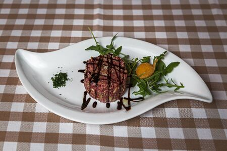 The tartare is a dish of French origin made from beef or horse meat which is served raw and cut with a knife into very small pieces. served with green rocket leaves, soft focus, Archivio Fotografico - 127506982