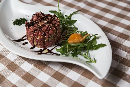 The tartare is a dish of French origin made from beef or horse meat which is served raw and cut with a knife into very small pieces. served with green rocket leaves, soft focus, Archivio Fotografico - 127506983