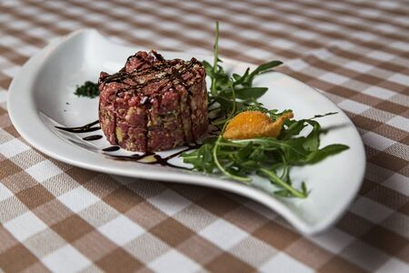 The tartare is a dish of French origin made from beef or horse meat which is served raw and cut with a knife into very small pieces. served with green rocket leaves, soft focus, Archivio Fotografico - 127506985