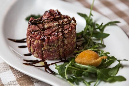 The tartare is a dish of French origin made from beef or horse meat which is served raw and cut with a knife into very small pieces. served with green rocket leaves, soft focus, Archivio Fotografico - 127506986