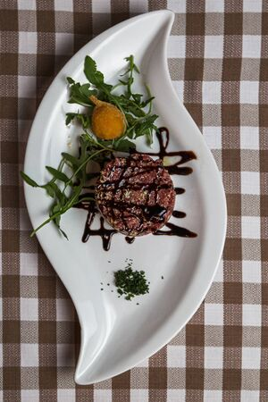 The tartare is a dish of French origin made from beef or horse meat which is served raw and cut with a knife into very small pieces. served with green rocket leaves, soft focus, Archivio Fotografico - 127506990