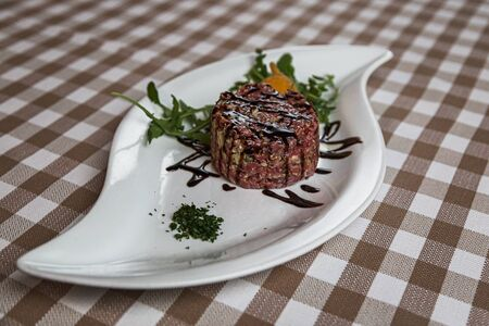 The tartare is a dish of French origin made from beef or horse meat which is served raw and cut with a knife into very small pieces. served with green rocket leaves, soft focus, Archivio Fotografico - 127506989