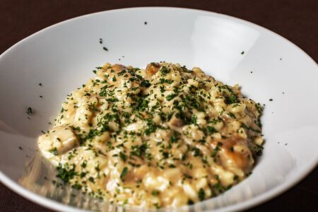 Italian Risotto with mushrooms on a dark background, soft and selective focus. Archivio Fotografico - 127507145