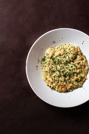 Italian Risotto with mushrooms on a dark background, soft and selective focus. Archivio Fotografico - 127507143