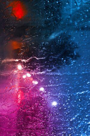 Rain through the glass with neon light Archivio Fotografico - 129244810