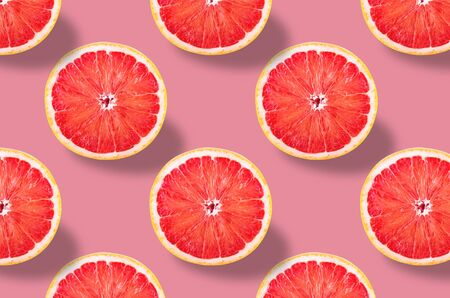 Fruit pattern. Colorful fresh slices grapefruits texture on rose pastel background. From top view. full depth of field. Archivio Fotografico - 129244825